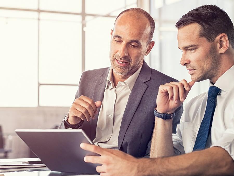 dois homens executivos em reuniao sentados a mesa com tablet