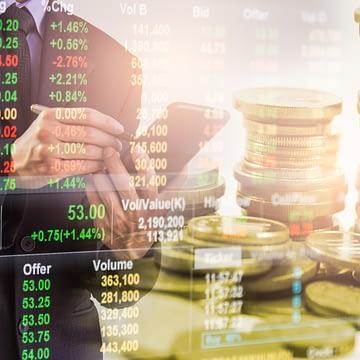 painel com cotações da bolsa de valores com homem ao celular e moedas ao fundo