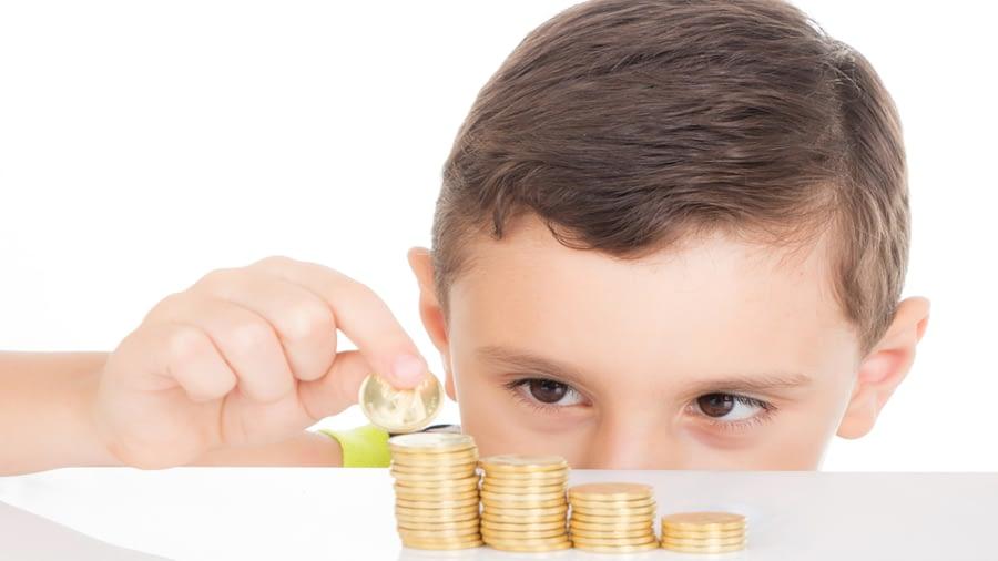 menino com quatro pilhas de moedas
