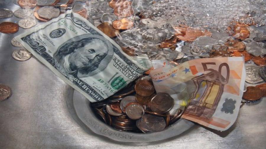 notas e moedas de dólar e euro caindo pelo ralo