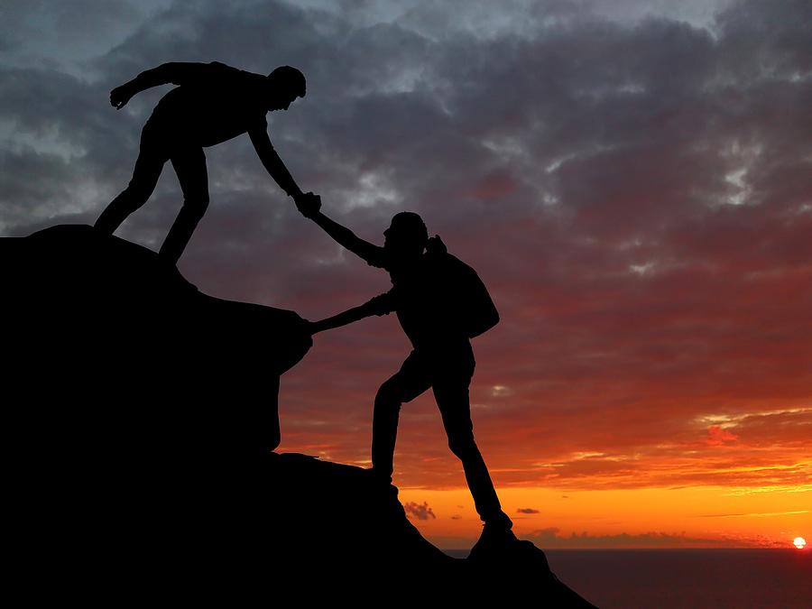 Homens se ajudando a escalar montanha dando as mãos