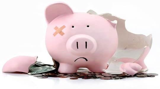 porquinho rosa quebrado com dinheiro no chão