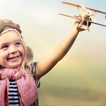 criança feliz com avião na mão